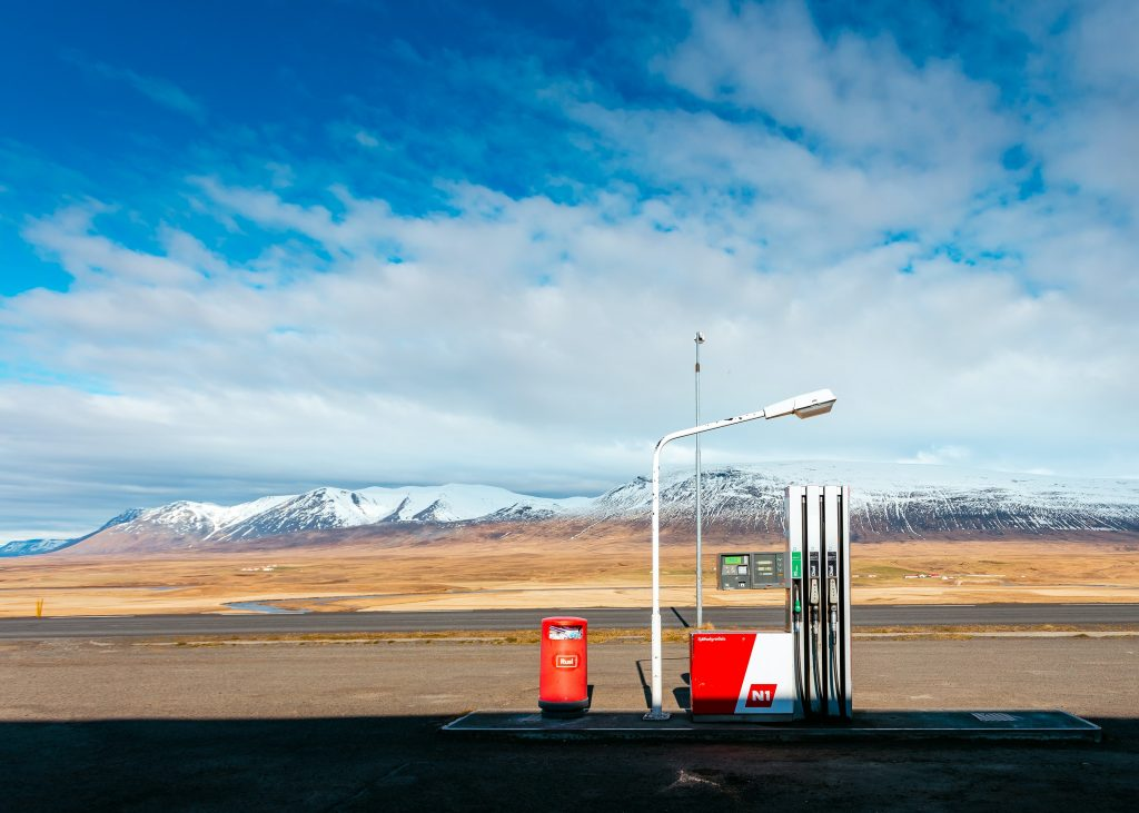 Tiny gas station in the middle of the high way with mountains in the background