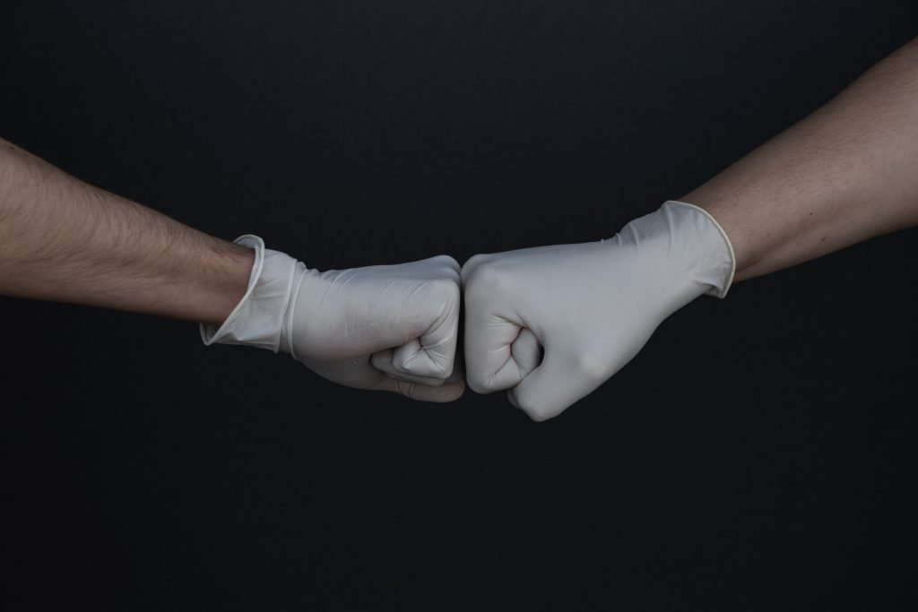 A fist bump with white gloves